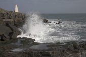 Waves crashing on to rocky shore near the Obelisk at Portland Bill Dorset England