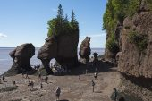 Rocks and visitors on the ocean floor at the edge of the bay of Fundy Hopewell Rocks New Brunswick Canada August 2016