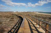 Sand dunes and beach Praia do Alvor with Alvor beyond Algarve Portugal