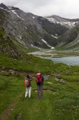 Walkers beside Lac Oulettes Ossoue Valley Pyrenees National Park France